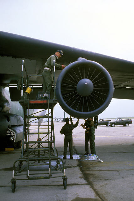 Staff Sergeant (SSGT) Jimmy Olson checks and services the oil in a C-141B Starlifter engine as other technicians work underneath
