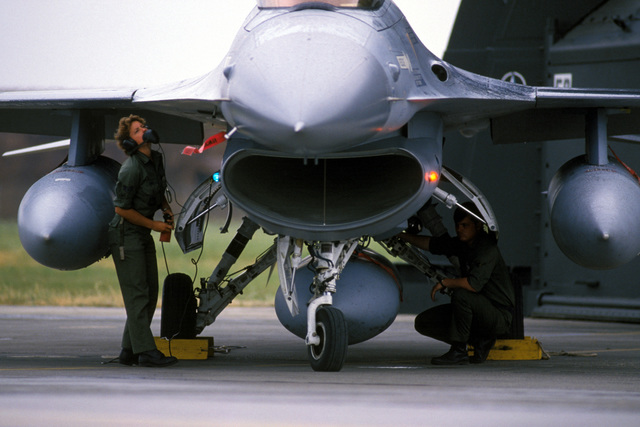 Staff Sergeant (SSGT) Kari Sims and Colonel (COL) Walter Hersman conduct preflight checks on a 612th Tactical Fighter Squadron F-16 Fighting Falcon aircraft