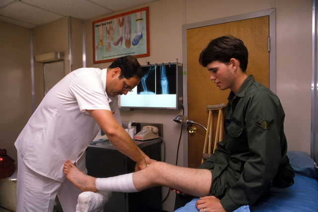 Staff Sergeant (SSGT) Kevin Gray, an orthopedic technician, applies a cast to the broken kneecap of AIRMAN (AMN) Michael Dupuis at the US Air Force Hospital Incirlik