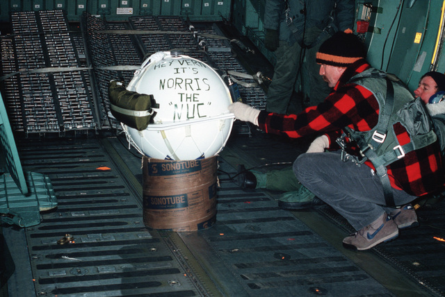 Dick Morita, University of Washington Polar Science Center, checks one of the 10 weather buoys to be dropped out of a C-141B Starlifter aircraft during a mid-winter airdrop over the South Pole