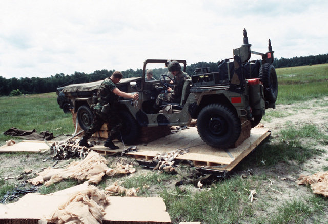 Members of the 1ST Battalion 39th Field Artillery remove an M151 light utility vehicle from its drop platform during an XVIII Airborne Corps emergency deployment readiness exercise
