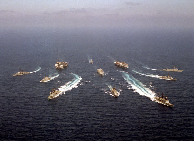 An aerial view of various ships underway in formation. They are, counter-clockwise from left: guided missile destroyer WILLIAM V. PRATT (DDG-44), frigate USS TRUETT (FF-1095), destroyer USS CONOLLY (DD-979), guided missile cruiser USS JOSEPHUS DANIELS (CG-27), destroyer USS COMTE DE GRASSE (DD-974), frigate USS W. S. SIMS (FF-1059), guided missile frigate USS DOYLE (FFG-39), aircraft carrier USS SARATOGA (CV-60), guided missile frigate USS HAWES (FFG-53), aircraft carrier USS KITTY HAWK (CV-63) and replenishment oiler USS KALAMAZOO (AOR-6), center