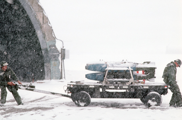 Senior AIRMAN (SRA) Gregory Beasley and AIRMAN First Class (A1C) David Kiraly, both of the 8th Equipment Maintenance Squadron, maneuver a bomb cart across the flight line during a snowstorm