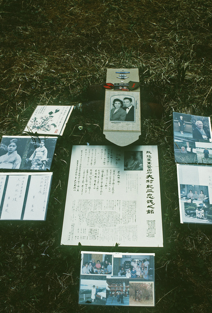 Pictures of World War II Japanese and American veterans and their families are displayed around the burial marker of Commander (CDR) Yasuso Yamazaki during dedication of a peace memorial honoring all Japanese and Americans who lost their lives during the