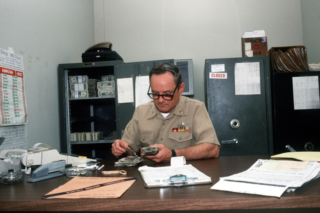 SENIOR CHIEF Chandler, leading chief petty officer at the disbursing section of the Personnel Support Detachment, keeps track of Italian lire and American dollars