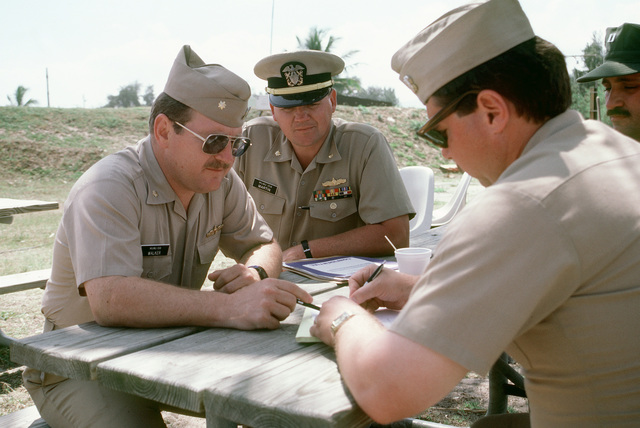 U.S. Navy officers of Mobile Inshore Undersea Warfare Unit 1519 discuss plans during inshore undersea warfare operations