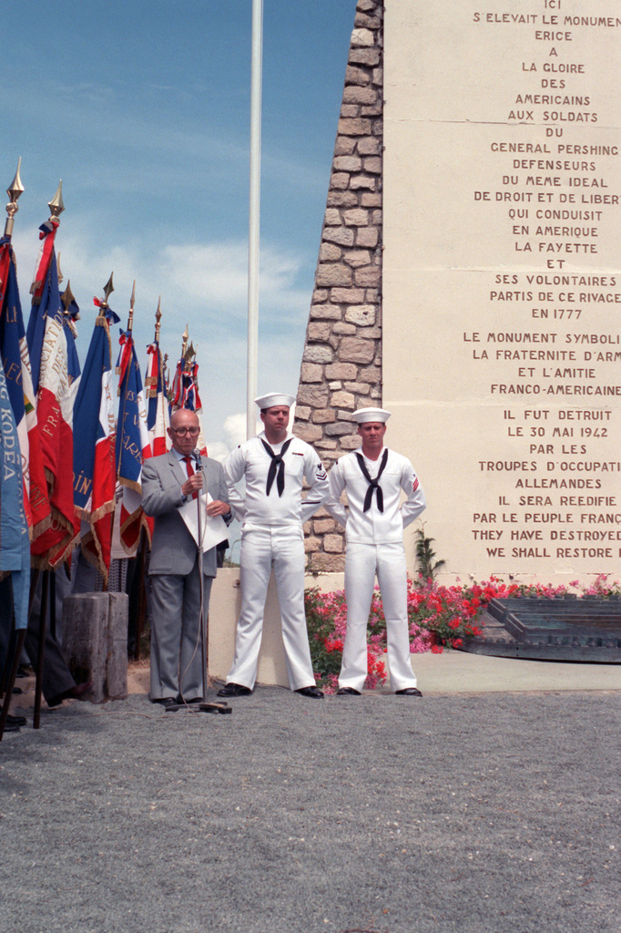 US Navy sailors stand at parade rest next to a distinguished guest during the ceremony commemorating the 70th anniversary of the entry of the United States into World War I.  The sailors are crew members aboard the guided missile frigate USS ANTRIM (FFG 20) and are standing beside a monument honoring French and American military cooperation over a period of 200 years