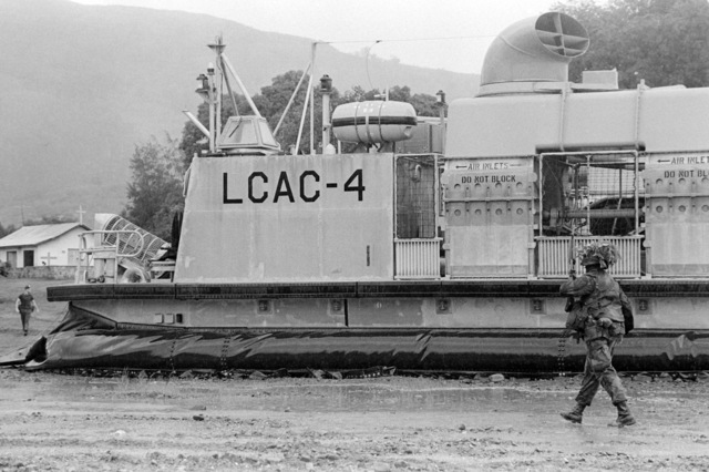 A Marine from Company A, 1ST Battalion, 9th Marine Regiment, walks by an Assault Craft Unit 5 (ACU 5) air-cushion landing craft LCAC4 during an amphibious assault exercise