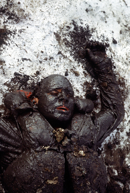 A mud-covered trainee lies exhausted in the sand during Basic Underwater Demolition/SEAL (BUD/S) training