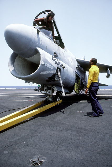 A plane captain and plane director discuss the positioning of an Attack Squadron 72 (VA-72) A-7E Corsair II aircraft during flight operations aboard the nuclear-powered aircraft carrier USS DWIGHT D. EISENHOWER (CVN-69). Drawbars, visible at the front of the aircraft, secure the plane to an MD-3A tow tractor