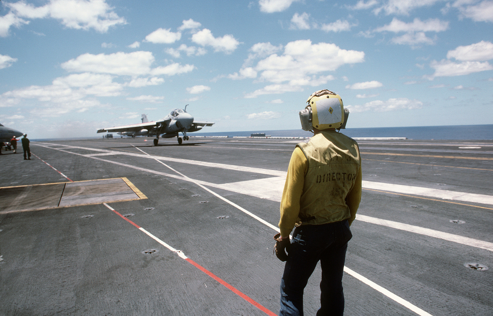 """A plane director watches as an A-6E Intruder aircraft executes a""""touch and go""""takeoff from the nuclear-powered aircraft carrier USS DWIGHT D. EISENHOWER (CVN 69)"""