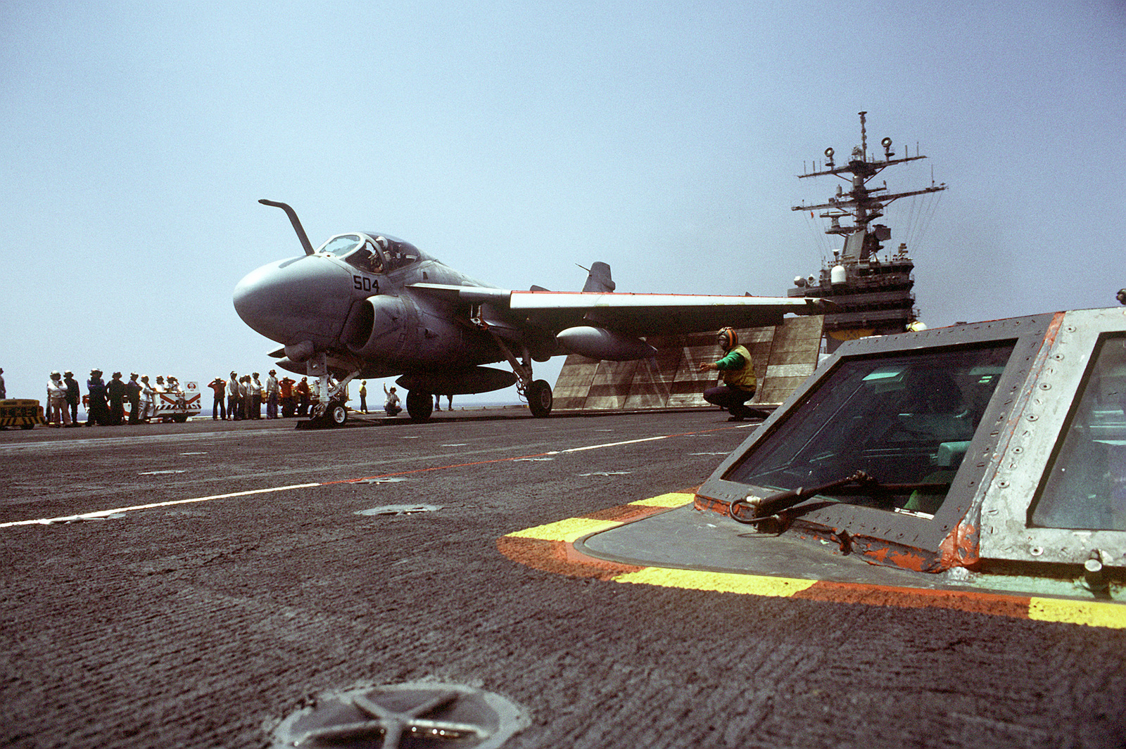 A safety observer signals instructions to an A-6E Intruder pilot during flight operations aboard the nuclear-powered aircraft carrier USS DWIGHT D. EISENHOWER (CVN-69). The integrated catapult control system is in the foreground