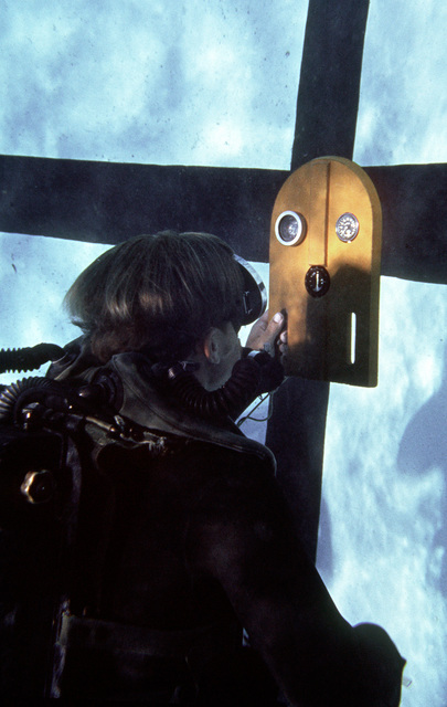 A trainee checks a set of gauges while underwater during Basic Underwater Demolition/SEAL (BUD/S) training