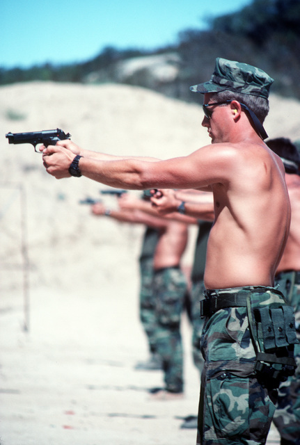 A trainee fires an M-9 9mm pistol on the pistol range during Basic Underwater Demolition/SEAL (BUD/S) training