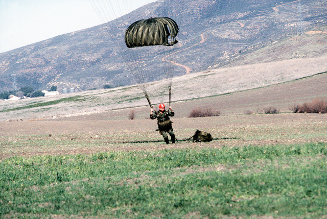 A trainee parachutes to the ground during Basic Underwater Demolition/SEAL (BUD/S) training