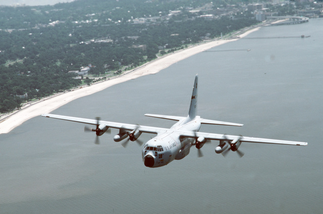 An air-to-air left front view of a WC-130H Hercules aircraft in flight over the Atlantic coast of Florida