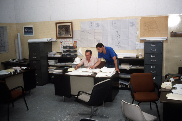 Antonio Verdirame, left, and Antonio Amitrano, local residents working as inspectors for the resident officer in charge of construction, review plans for the air station's new library