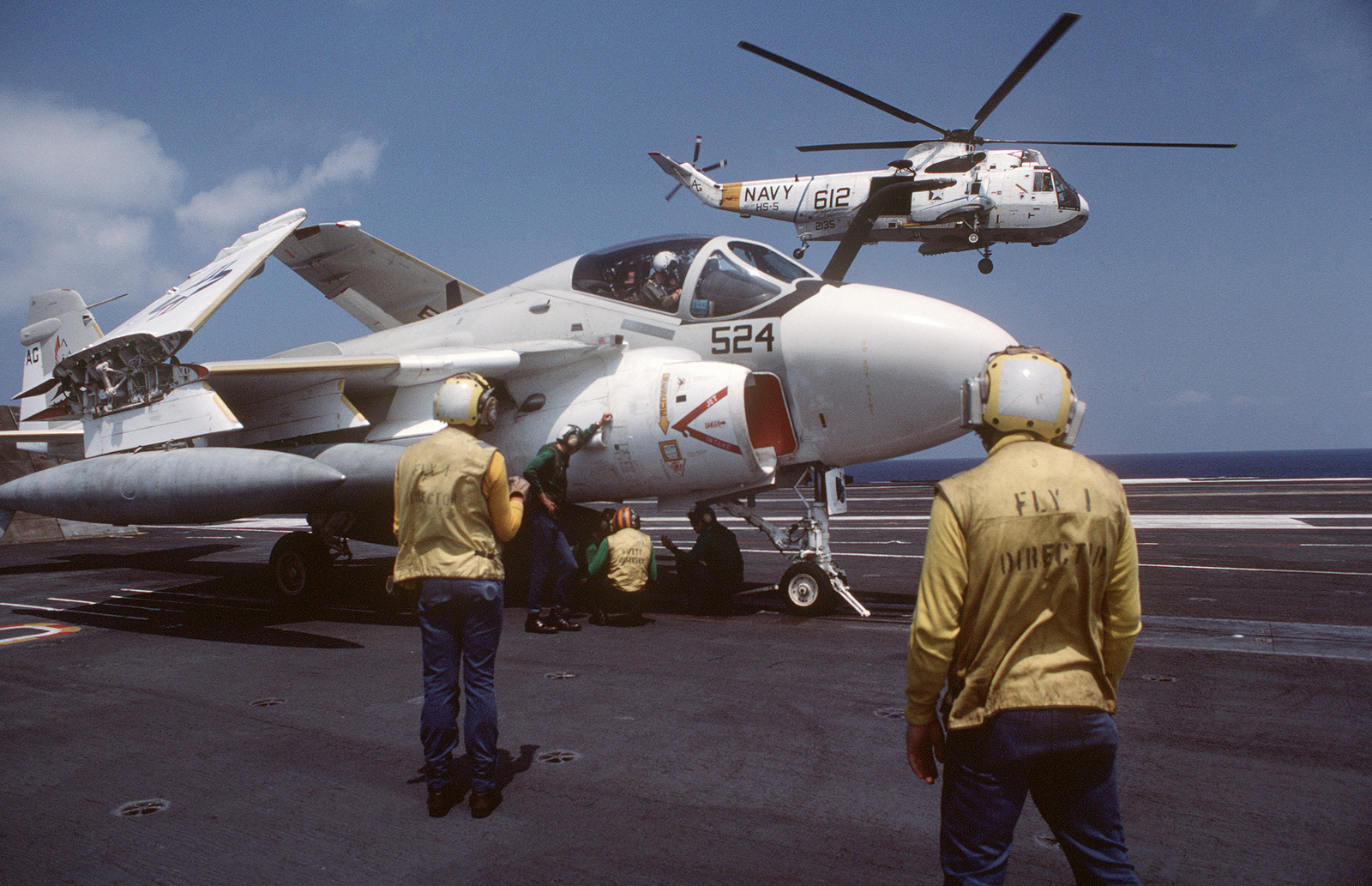 Catapult crewmen work beneath an A-6E Intruder aircraft aboard the nuclear-powered aircraft carrier USS DWIGHT D. EISENHOWER (CVN 69) as two plane directors stand by.  A Helicopter Anti-submarine Squadron 5 (HS-5) SH-3H Sea King helicopter is taking off in the background