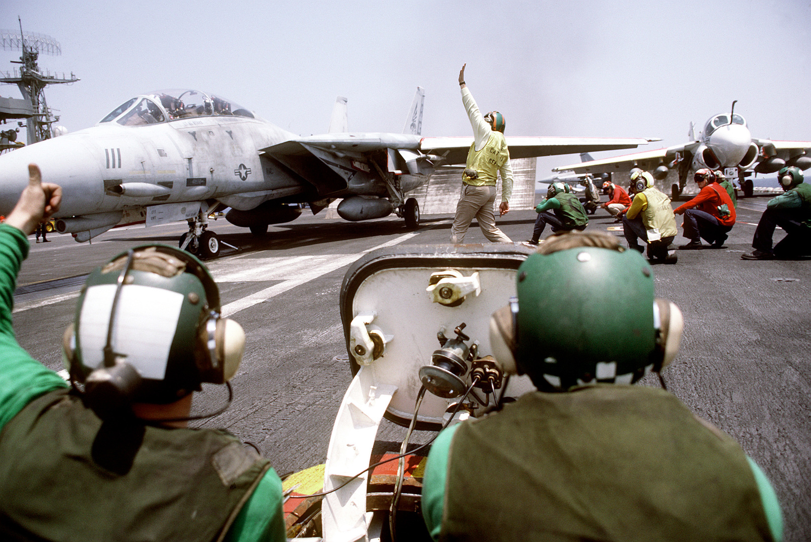 Crewmen prepare to launch an F-14A Tomcat aircraft on the flight deck of the nuclear-powered aircraft carrier USS DWIGHT D. EISENHOWER (CVN-69). An A-6E Intruder aircraft is parked in the background