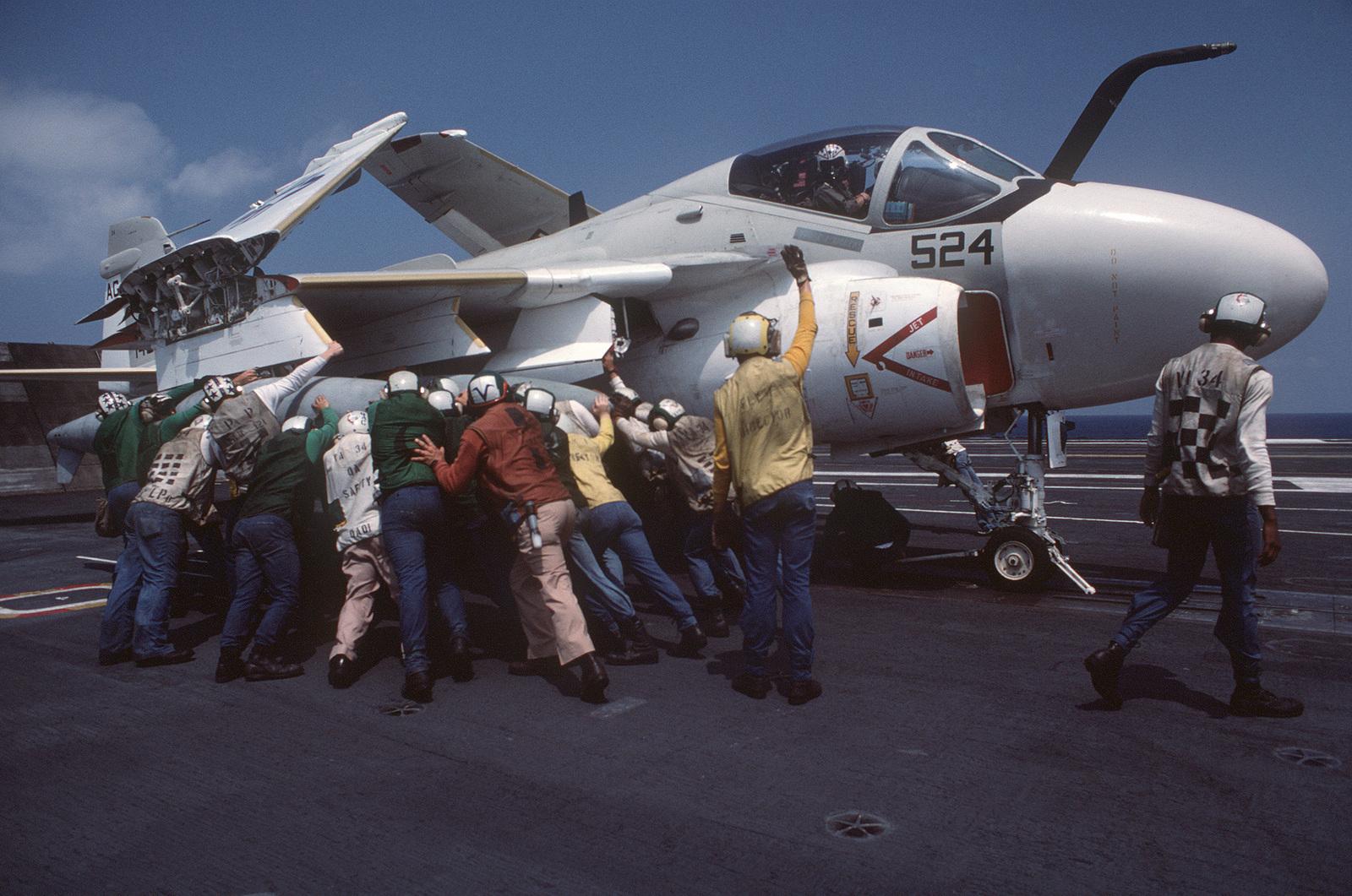 Flight deck crewmen push an A-6E Intruder aircraft into position on a catapult aboard the nuclear-powered aircraft carrier USS DWIGHT D. EISENHOWER (CVN 69)