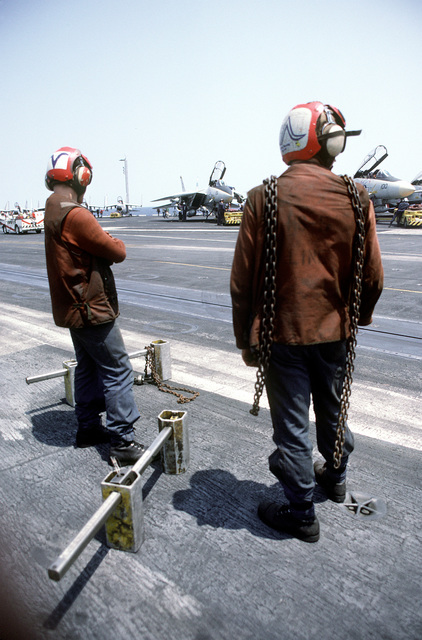 Flight deck crewmen stand by with chocks and tie-down chains during flight operations aboard the nuclear-powered aircraft carrier USS DWIGHT D. EISENHOWER (CVN-69)