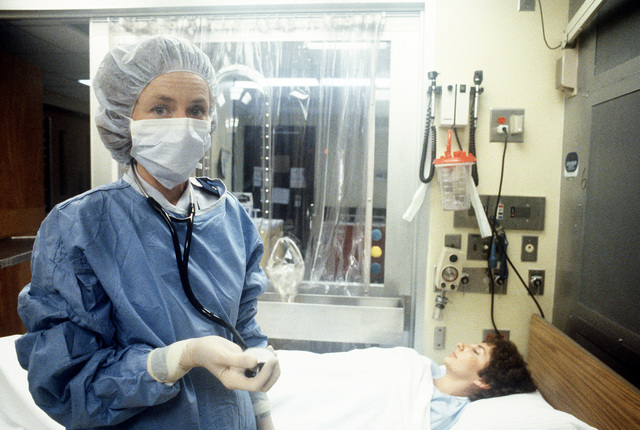 LT. COL. (Dr.) Mary Daly, chief of hematology and oncology at Wilford Hall U.S. AIr Force Medical Center, stands in a laminar airflow room in the bone marrow transplant unit. LT. COL. Daly is wearing a sterile cap, gown , mask, gloves and booties in preparation for examining patients in this room
