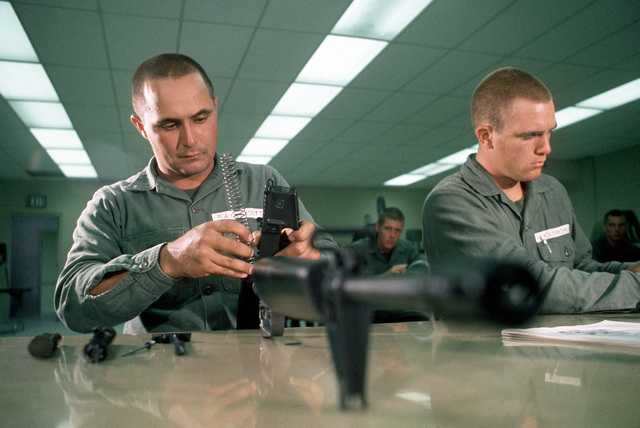 Trainees assemble M-16A1 rifles in a classroom during Basic Underwater Demolition/SEAL (BUD/S) training