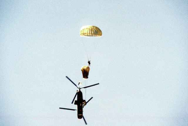 Trainees parachute from a CH-46 Sea Knight helicopter during Basic Underwater Demolition/SEAL (BUD/S) training