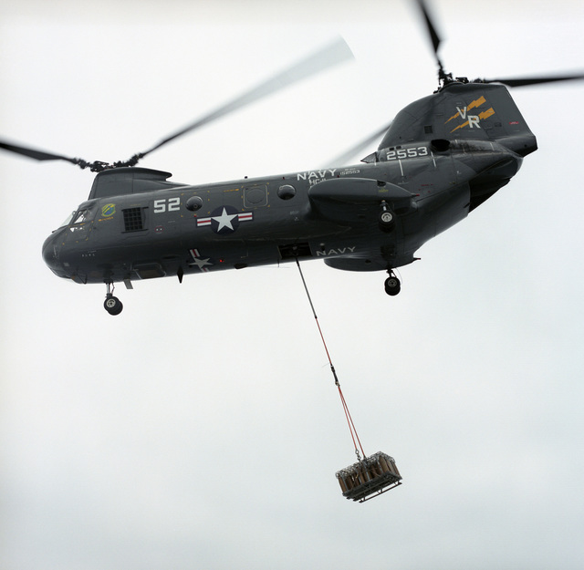 A US Navy (USN) CH-46 Sea Knight, Helicopter Combat Support Squadron Eleven (HC-11), Gunbearers, Naval Air Station North Island (NASNI), departs with a load of 5-inch projectiles during a vertical replenishment (VERTREP) from a supply ship while underway on the Pacific Ocean