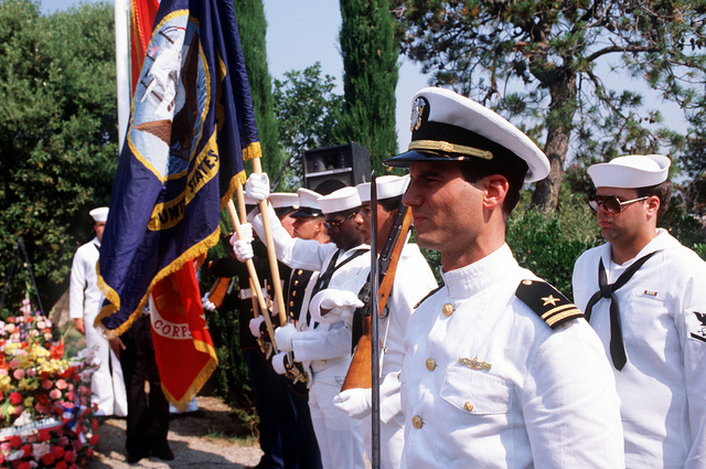 A junior naval officer draws his sword in salute as a color guard presents the colors at the Liberator Monument during the Festival American, a French and United Services Organization (USO) salute to Independence Day. The Liberator Monument marks the mountain crash site of a B-24 Liberator aircraft and honors the American pilot who died after diverting the severely damaged bomber from the city during World War II