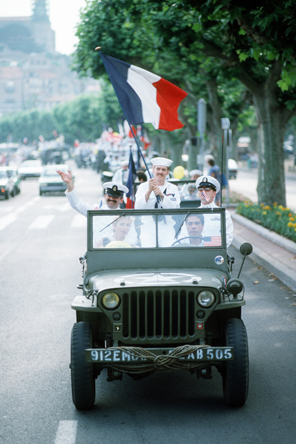 An American sailor waves the French flag from a jeep in a parade of authentic World War II vehicles during Festival American, a French and United Services Organization (USO) celebration of Independence Day. Festival events also include a concert for residents and visitors and a gala dinner-dance for special guests