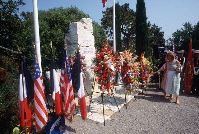Guests admire wreaths placed in front of the Liberator Monument during the Festival American, a French and United Services Organization (USO) celebration of Independence Day. The Liberator Monument marks the mountain crash site of a B-24 Liberator aircraft and honors the American pilot who died after diverting the severely damaged bomber from the city during World War II