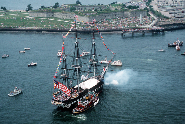 The 44-gun sail frigate USS CONSTITUTION fires two 24-pound long guns (fitted for 40mm rounds) in a 21-gun salute to the nation off Castle Island Park. After the salute the ship will be returned to its berth facing the opposite way to help it weather evenly and preserve the wood