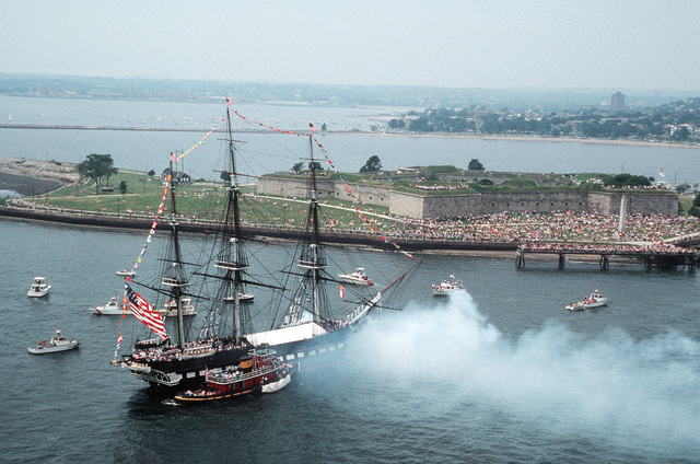 The 44-gun sail frigate USS CONSTITUTION fires two 24-pound long guns (fitted for 40 mm rounds) in a 21-gun salute to the nation off Castle Island Park.  After the salute the ship will be returned to its berth facing the opposite way to help it weather evenly and preserve the wood
