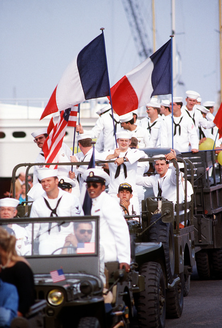 U.S. Navy personnel hold American and French flags and wave to the crowd in a parade of authentic World War II vehicles during Festival American, a French and United Services Organization (USO) celebration of Independence Day. Festival events also include a concert for residents and visitors and a gala dinner-dance for special guests