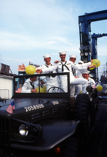 U.S. Navy personnel pose for the camera while standing in an authentic World War II personnel carrier during Festival American, a French and United Services Organization (USO) celebration of Independence Day. Festival events also include a concert for residents and visitors and a gala dinner-dance for special guests