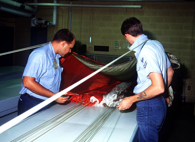 Aircrew Survival Equipmentman 3rd Class L. Dolleman, left, and Aircrew Survival Equipmentman 2nd Class T. Haff inspect the shroud lines and canopy of a parachute in an Aircraft Intermediate Maintenance Department (AIMD) shop