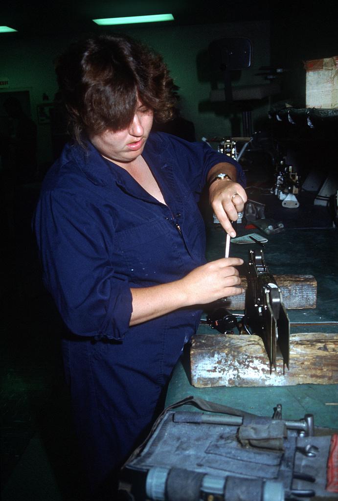 Aviation Ordnanceman M. Delrio repairs a bomb release unit in an Aircraft Intermediate Maintenance Department (AIMD) shop