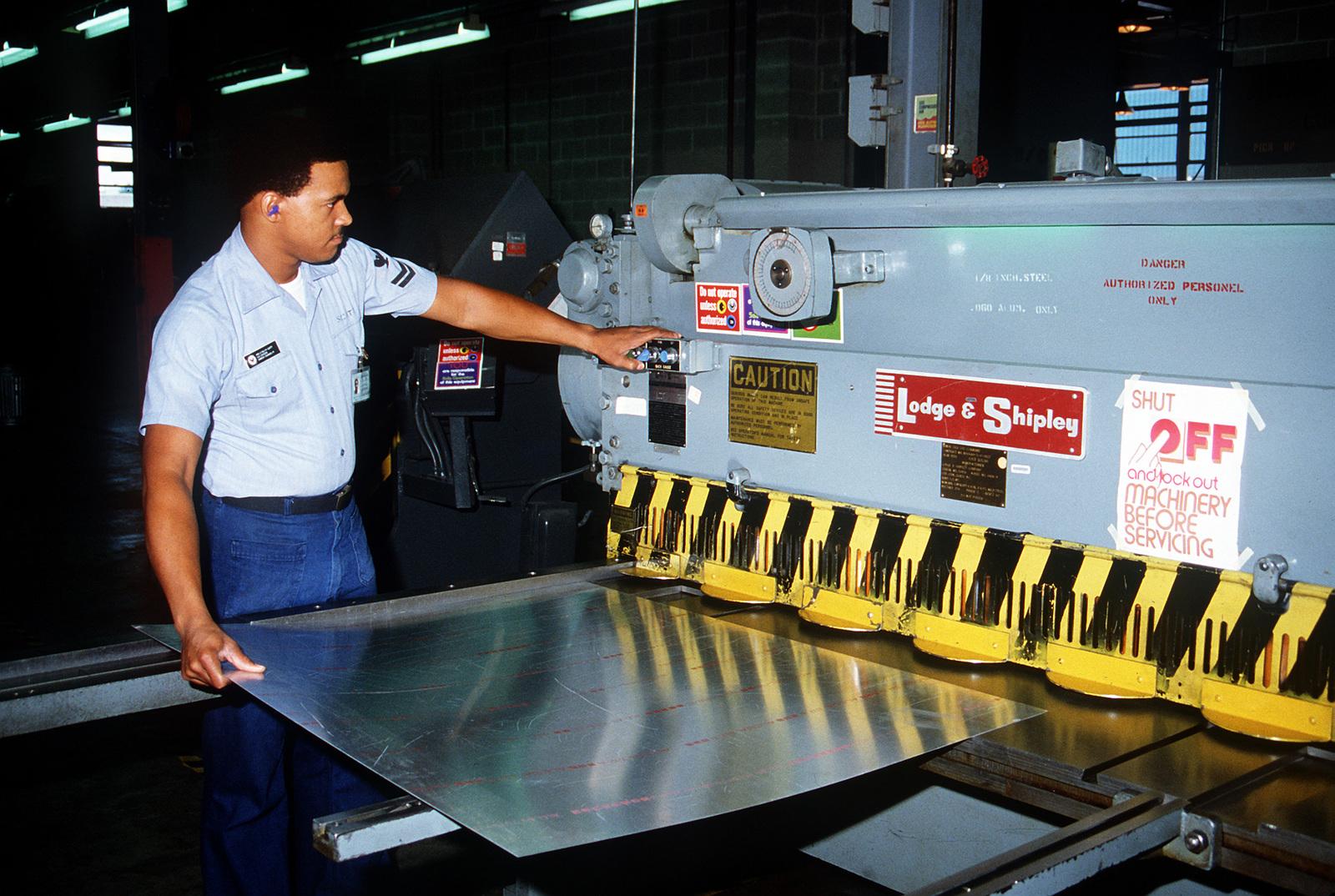 Aviation Structual Mechanic S (Structures) 2nd Class Ralph Scott slides a section of sheet metal into a power shear in an Aircraft Intermediate Maintenance Department (AIMD) shop