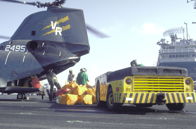 Flight deck crewmen unload mail from a Helicopter Combat Support Squadron 11 (HC-11) HH-46A Sea Knight helicopter aboard the aircraft carrier USS KITTYHAWK (CV-63). An MD-3A tow tractor is in the foreground