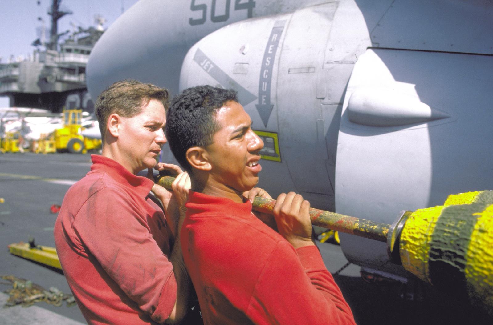 Ordnancemen of Attack Squadron 165 (VA-165) mount a Mark 82 500 pound high-drag bomb onto an A-6E Intruder aircraft aboard the aircraft carrier USS KITTY HAWK (CV-63)