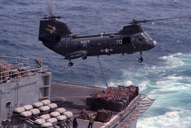 A crewman guides the pilot of a Helicopter Combat Support Squadron 11 (HC-11) HH-46A Sea Knight helicopter as supplies are retrieved from the fast Combat Support Ship USS CAMDEN (AOE 2) during vertical replenishment operations