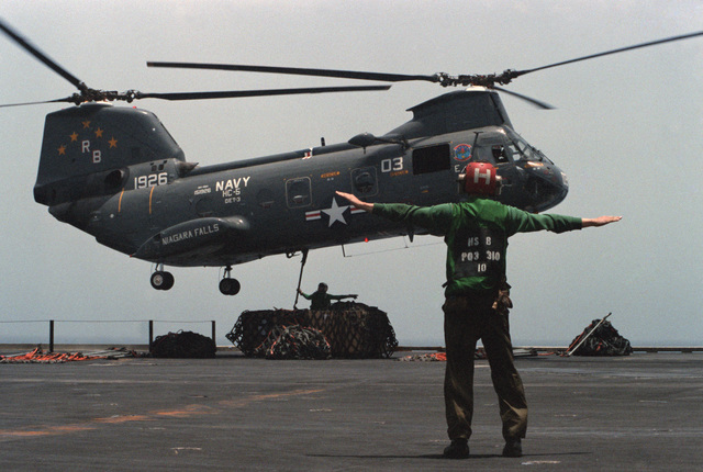 A crewman guides the pilot of a Helicopter Combat Support Squadron 5 (HC-5) HH-46A Sea Knight helicopter as supplies are retrieved from the Combat Stores Ship USS NIAGARA FALLS (AFS 3) during vertical replenishment operations