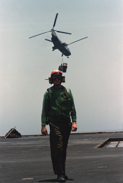 A crewman stands by aboard the Combat Stores Ship USS NIAGARA FALLS (AFS 3) as an HH-46A Sea Knight helicopter takes off with a load of supplies during vertical replenishment operations