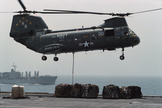 A Helicopter Combat Support Squadron 5 (HC-5) HH-46A Sea Knight helicopter delivers supplies from the Combat Stores Ship USS NIAGARA FALLS (AFS 3), seen in the background, during vertical replenishment operations