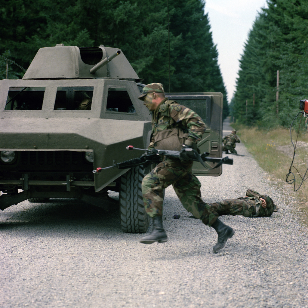 """A cadet carrying two M16A1 rifles runs around the side of a high mobility multi-purpose wheeled vehicle used as a mock tank during an assault as part of the 4th Army ROTC Region""""Camp Adventure"""" Advanced Camp'87"""