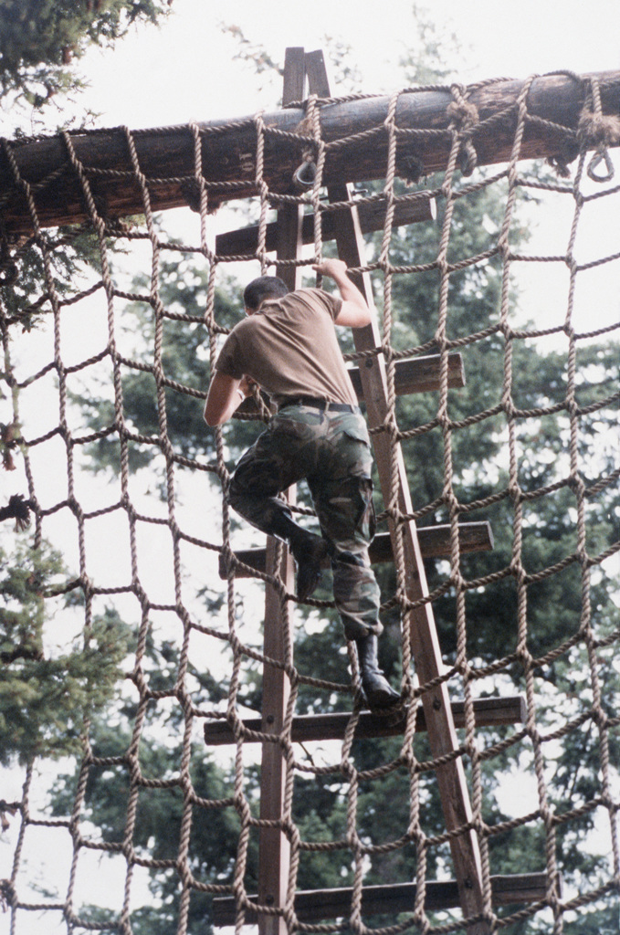 """A cadet climbs a rope ladder on the obstacle course during the 4th Army ROTC Region""""Camp Adventure""""ADVANCED CAMP'87"""