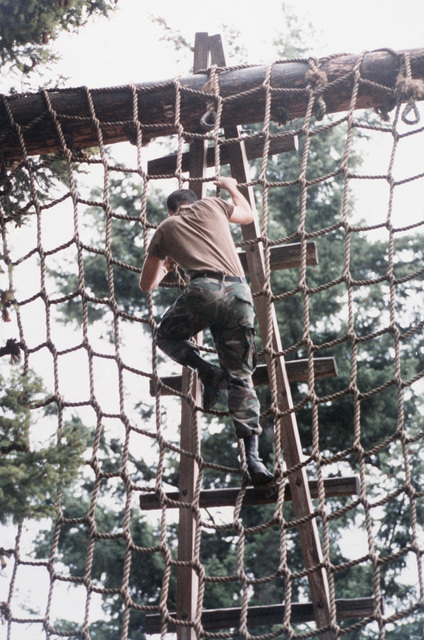 "A cadet climbs a rope ladder on the obstacle course during the 4th Army ROTC Region""Camp Adventure""ADVANCED CAMP'87"