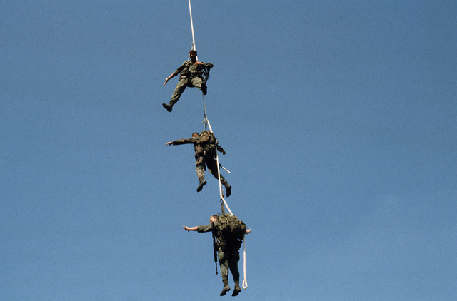Three students at the Scout Sniper Instructor School practice special patrol insertion/extraction (SPIE) rig techniques during a training exercise