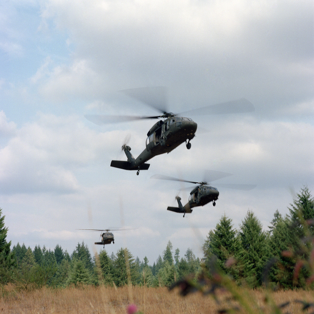 """Three UH-60 Black Hawk (Blackhawk) helicopters transport cadets during an air assault mission as part of the 4th Army ROTC Region""""Camp Adventure"""" Advanced Camp'87"""